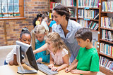 Cute pupils and teacher looking at computer in library