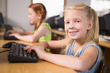 Cute pupil in computer class smiling at camera