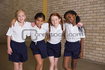 Cute pupils smiling at camera in PE uniform