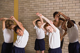 Cute pupils warming up in PE uniform
