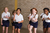 Cute pupils warming up in PE uniform