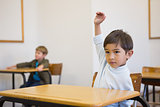 Pupil raising his hand at his desk