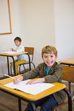 Pupil writing in notepad at his desk smiling at camera