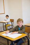 Pupil writing in notepad at his desk smiling at camera