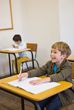 Pupil writing in notepad at his desk smiling