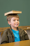 Happy pupil balancing book on his head at desk