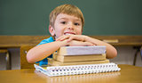 Happy pupil leaning on books at desk