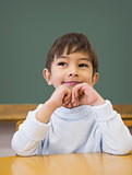 Cute pupil thinking at desk in classroom