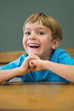 Happy pupil sitting at desk in classroom