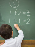 Cute pupil writing maths on chalkboard