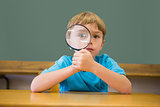 Cute pupil smiling at camera in classroom holding magnifying glass