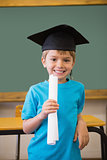 Cute pupil in mortar board smiling at camera in classroom