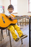 Cute pupil playing guitar in classroom