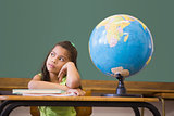 Cute pupil thinking in classroom with globe
