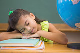Cute pupil napping in classroom with globe