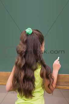 Cute pupil standing in classroom writing on chalkboard