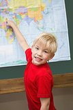 Cute pupil smiling at camera in classroom pointing to map