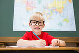 Cute pupil smiling at camera in classroom at his desk