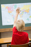 Cute pupil raising hand in classroom at his desk