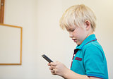 Cute pupil using smartphone in classroom