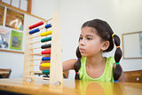 Cute pupil using abacus in classroom