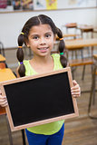 Cute pupil holding chalkboard in classroom