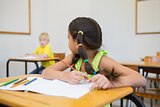 Cute pupils colouring at desks in classroom