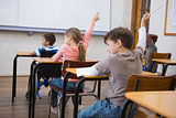 Pupils raising their hands during class