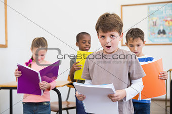 Classmates reading from notepads in classroom