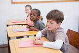 Cute pupils listening attentively in classroom