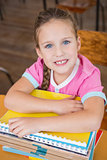 Cute pupil smiling at camera in classroom