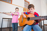 Cute pupils playing flute and guitar in classroom
