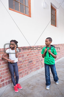 Cute pupil talking on her smartphone in hallway