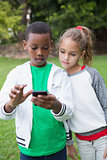 Cute little children looking at smartphone