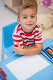 Cute little boy sitting at desk