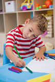 Cute little boy drawing at desk