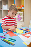 Cute little boy folding paper shapes in classroom