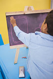 Cute little boy drawing on chalkboard