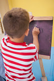Cute little boy drawing on chalkboard