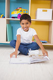 Cute little boy sitting on floor reading in classroom