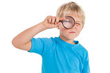 Cute little boy looking through magnifying glass