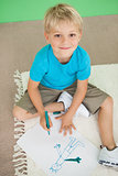 Cute little schoolboy smiling at camera while drawing