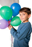 Happy little boy holding bunch of balloons