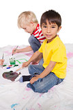 Happy little boys painting on the floor