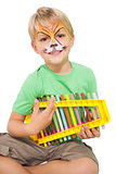 Happy little boy in tiger face paint playing xylophone
