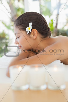 Beautiful brunette relaxing on massage table with salt scrub on back