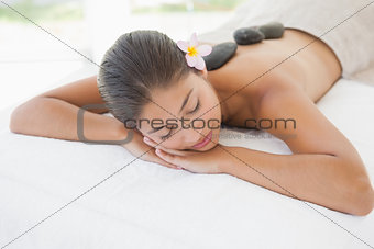 Beautiful brunette enjoying a hot stone massage