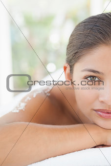 Beautiful brunette lying on massage table with salt scrub on back