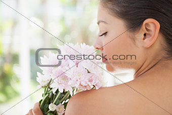 Beautiful brunette smelling bouquet of pink flowers