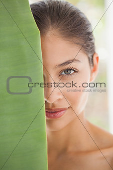 Beautiful brunette smiling at camera behind leaf